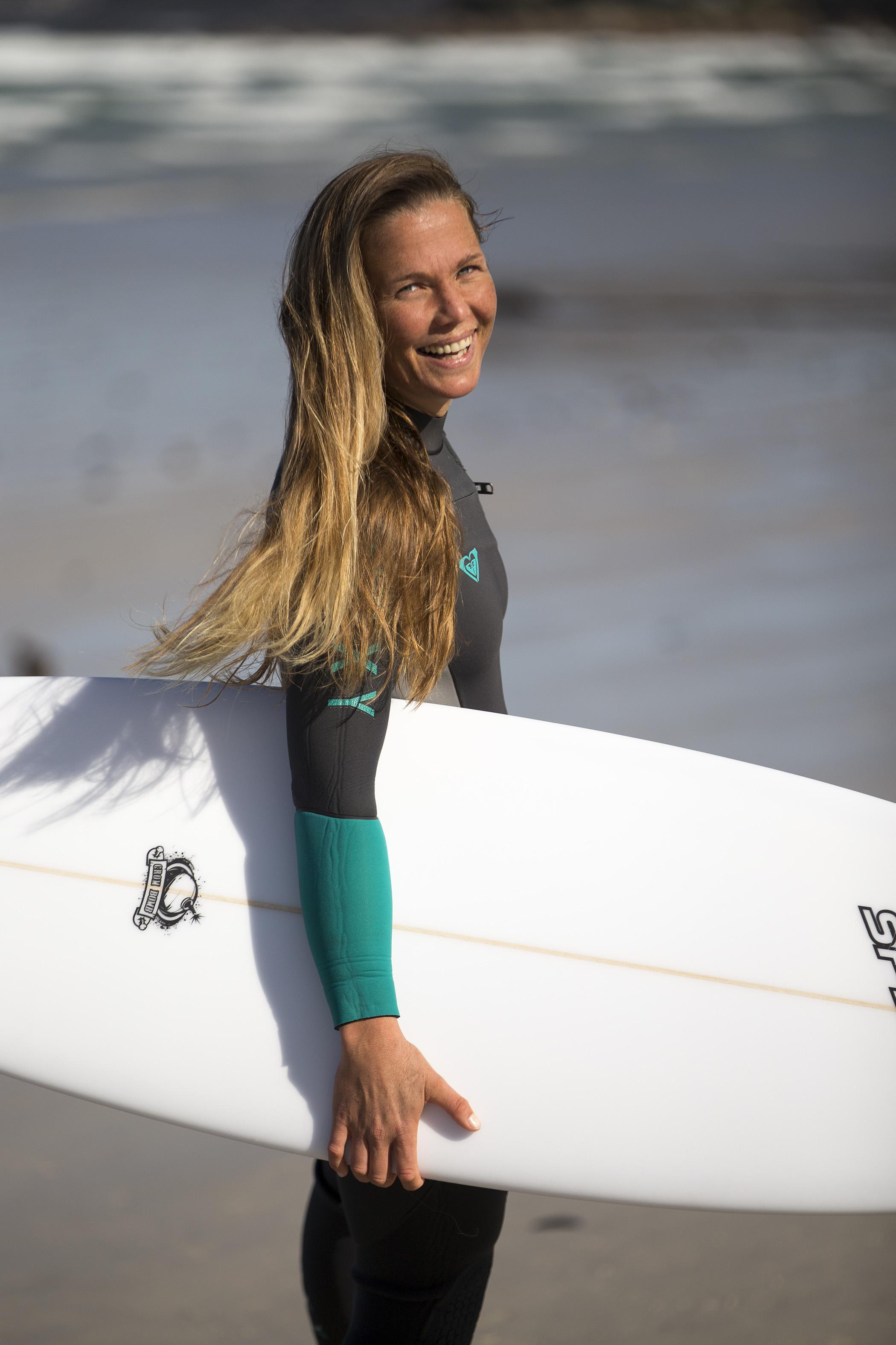 Roxy Davis holding a white surfboard